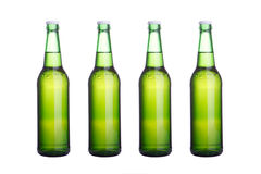 Quatre bouteilles à bière vertes sur le blanc Image libre de droits