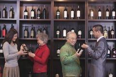 Quatre bouteilles de vin de examen de personnes à un magasin de vin Photos libres de droits