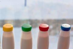 Quatre bouteilles de yaourt avec la couleur couvrent la position dans la ligne au windowsil Images stock
