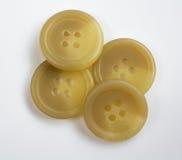 Quatre boutons en plastique crème empilés et d'isolement sur le blanc Photographie stock libre de droits