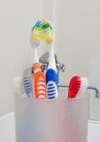 Quatre brosses à dents dans un verre Photos libres de droits