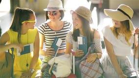 Quatre brunes portant l'habillement d'été se reposent dans la salle d'attente à l'aéroport avec des passeports et des billets ded clips vidéos