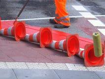 Quatre cônes menteur rouges du trafic et un cantonnier peignant une rue image stock