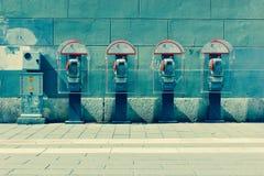 Quatre cabines de téléphone par le mur Photographie stock