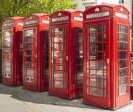Quatre cabines téléphoniques rouges à Londres Photographie stock libre de droits