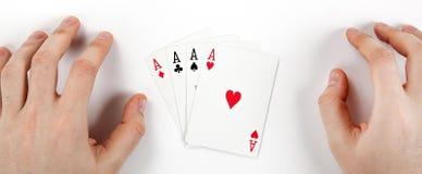 Quatre cartes avec des as sur la table et les mains blanches de l'homme Photographie stock