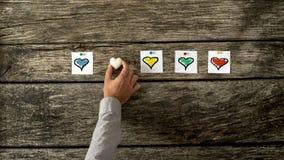 Quatre cartes blanches avec le coeur coloré différent forme sur eux pi Image stock