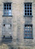 Quatre cassés et bricked vers le haut des fenêtres dans une épave ont abandonné la maison Photographie stock