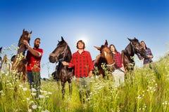 Quatre cavaliers heureux marchant avec leurs chevaux Photographie stock
