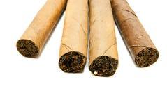 Quatre cigares cubains sur le blanc Images stock