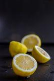 Quatre citrons sur la pierre noire Photographie stock libre de droits
