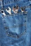 Quatre clés dans la poche de Jean bleue Image stock