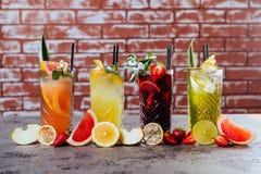 Quatre cocktails sur la table avec des fruits image stock