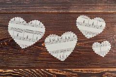 Quatre coeurs de papier sur le fond en bois Photo stock