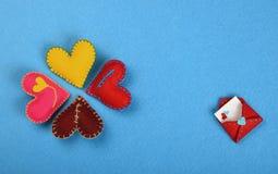 Quatre coeurs et lettres d'art de métier de feutre sur le bleu Photo stock