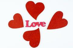 Quatre coeurs rouges et amour rose de mot d'isolement sur le fond blanc Images libres de droits