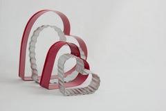 Quatre coupeurs en forme de coeur de biscuit se reposant des côtés Image libre de droits