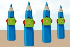 Quatre crayons colorés sur le chemin à l'école Photographie stock