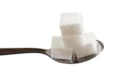 Quatre cubes en sucre sur une cuillère à café Photo libre de droits