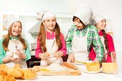 Quatre cuisiniers heureux de jeunes faisant la boulangerie de la pâte Photos libres de droits
