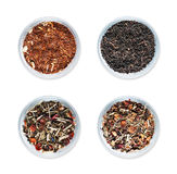 Quatre cuvettes avec différents types de thé sur le fond blanc d'isolement Photographie stock