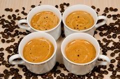 Quatre cuvettes blanches avec du café chaud photographie stock libre de droits
