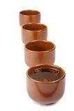 Quatre cuvettes de thé sur le blanc Photos stock