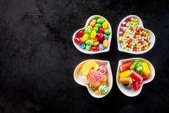 Quatre cuvettes en forme de coeur en céramique avec des sucreries Photo libre de droits