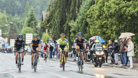 Quatre cyclistes montant sous la pluie Photographie stock libre de droits