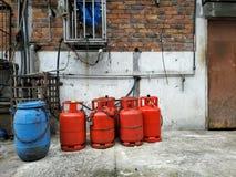 Quatre cylindres de gaz rouges sont au sol, près de la vieille maison photographie stock