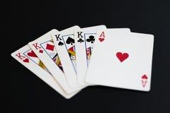 Quatre d'une sorte dans le jeu de cartes de tisonnier sur un fond noir Images stock