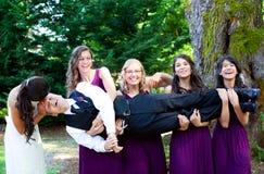 Quatre demoiselles d'honneur portant le marié dans leurs bras Images stock