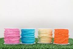 Quatre du fil coloré sur l'herbe avec le fond blanc Photographie stock libre de droits