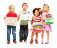 Quatre enfants avec des illustrations dans des leurs mains Photo stock