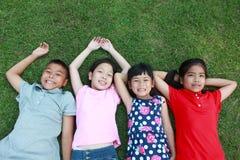 Quatre enfants ayant l'amusement dans le parc Photos stock