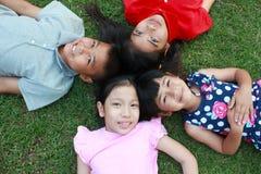 Quatre enfants ayant l'amusement dans le parc Photographie stock libre de droits
