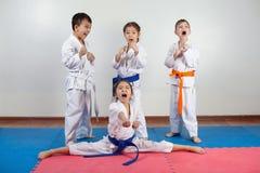 Quatre enfants démontrent des arts martiaux fonctionnant ensemble images stock