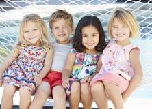 Quatre enfants détendant dans l'hamac de jardin ensemble Images stock