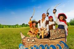 Quatre enfants dans des costumes de pirate derrière le bateau Images stock