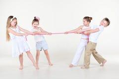 Quatre enfants dans des vêtements blancs trop serrent la corde rose Photos stock