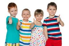 Quatre enfants gais tiennent ses pouces  Image libre de droits