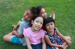 Quatre enfants jouant en parc Photographie stock