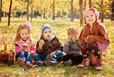 Quatre enfants jouant en parc d'automne avec des fruits Photo libre de droits