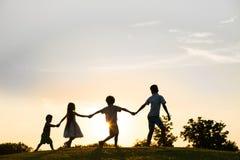 Quatre enfants jouent sur le coucher du soleil Photos stock