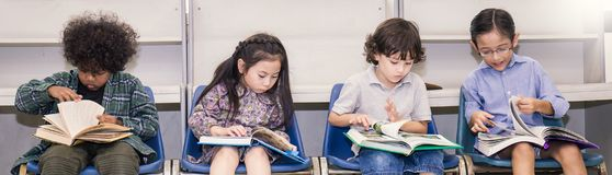 Quatre enfants lisant sur une chaise dans la salle de classe Image stock