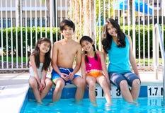 Quatre enfants par le côté de piscine Photographie stock libre de droits