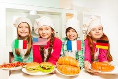 Quatre enfants représentant le repas de différents pays photo stock