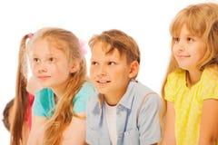 Quatre enfants s'asseyant dans une rangée souriant et écoutant Photos stock