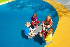 Quatre enfants s'asseyant sur la vue de carrousel à partir du dessus Image libre de droits