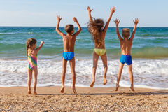 Quatre enfants sautant sur la plage Photographie stock